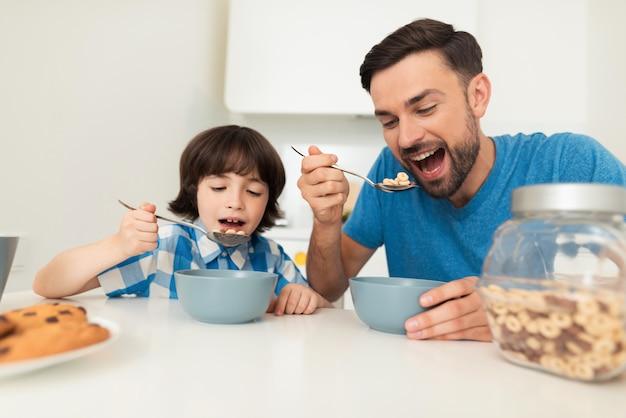 Tata i syn jedzą razem śniadanie w kuchni.