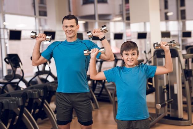 Tata i syn na siłowni robi ćwiczenia z hantlami.