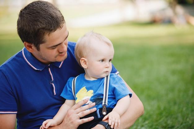 Tata i syn o blond włosach siedzą latem na zielonym trawniku