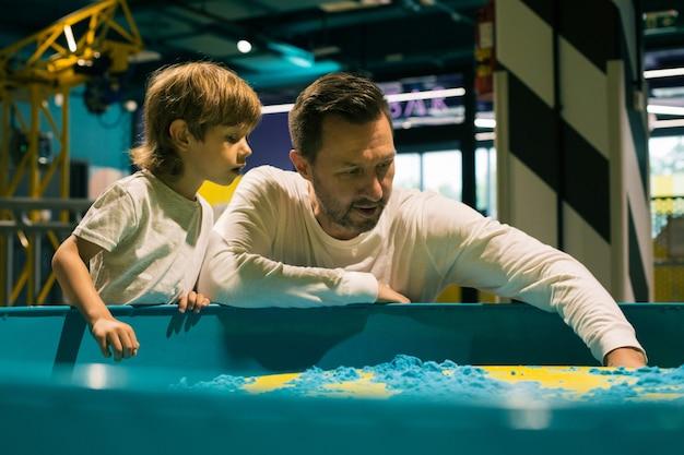 Tata i syn pasjonują się zabawą piaskiem kinetycznym w centrum rozwoju. rozwój umiejętności motorycznych. łagodzenie stresu i napięcia. wzajemne zrozumienie i wsparcie.
