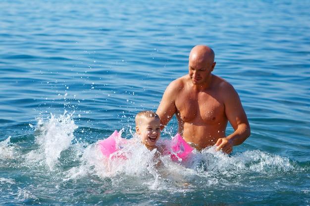 Tata i syn pływają w morzu, uczą się pływać, rodzinnego wakacje pojęcie