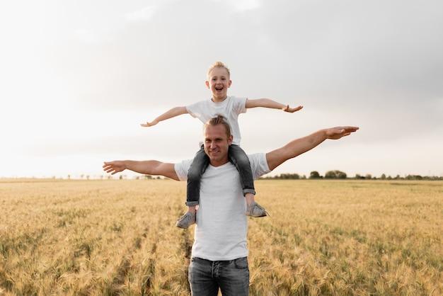 Tata i syn podróżują na piękne pola pszenicy.