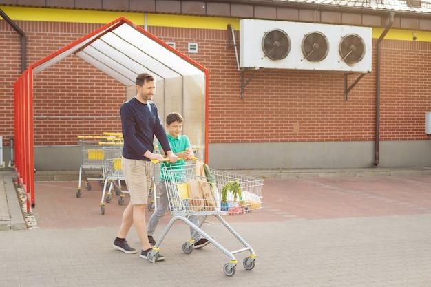 Tata i syn poszli razem na zakupy i idą do samochodu z wózkiem na zakupy, spędzają razem czas, koncepcja samotnego ojca