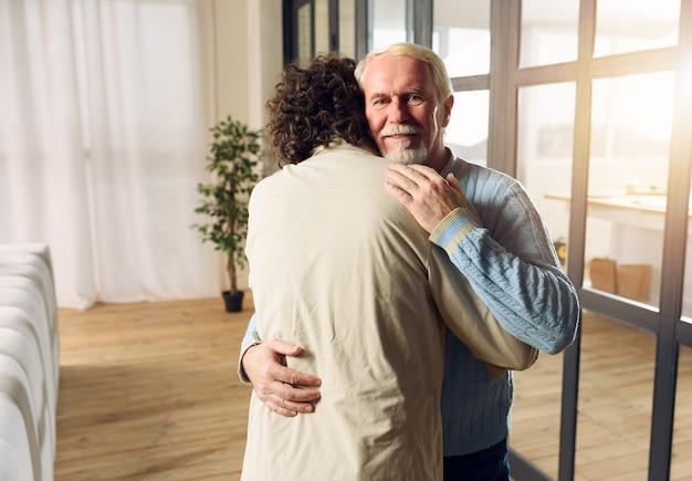 Tata i syn przytulają się w domu. pojęcie relacji rodzinnych