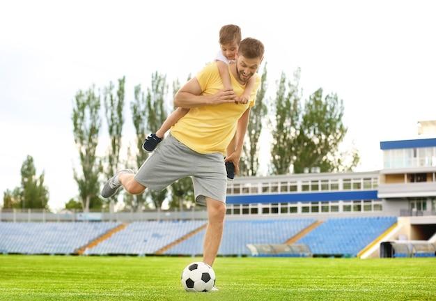 Tata i syn razem grają w piłkę nożną na stadionie