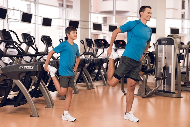 Tata i syn rozciągają nogi na siłowni.