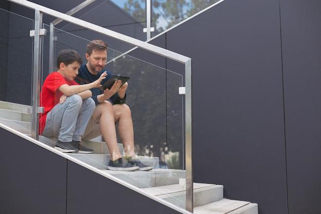Tata i syn siedzą na schodach ze szklanymi balustradami i rozmawiają o nowych trendach za pomocą urządzenia mobilnego - tabletu