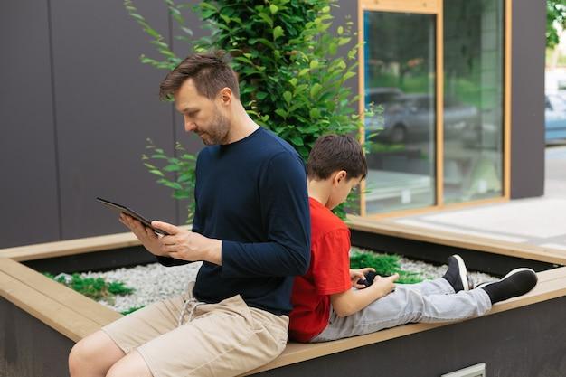 Tata i syn w miejskich parkach wśród betonowych domów używają modów do wspólnego spędzania czasu