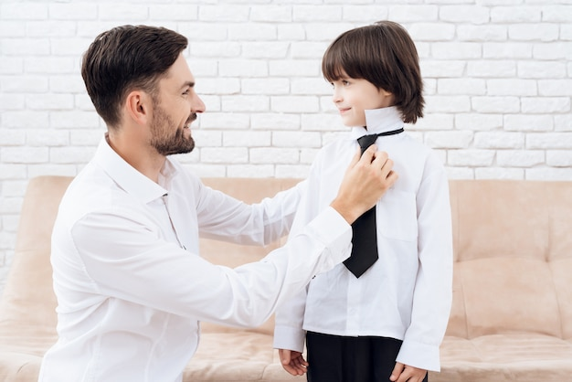 Tata i syn w tych samych ubraniach. tata pomaga swojemu synowi.