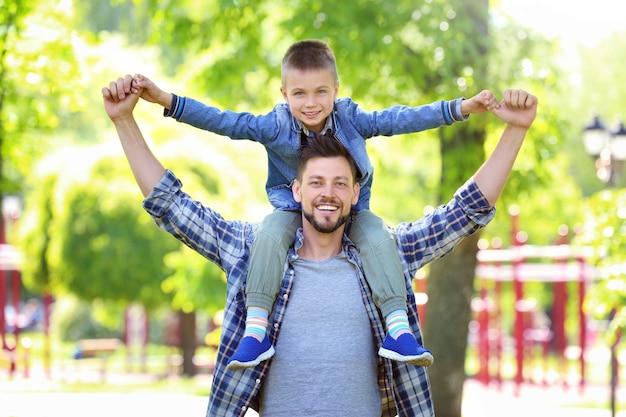 Tata i syn w zielonym parku w słoneczny dzień