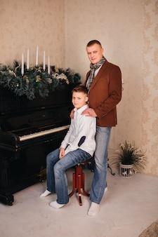 Tata i syn wokół pianina ozdoby świąteczne