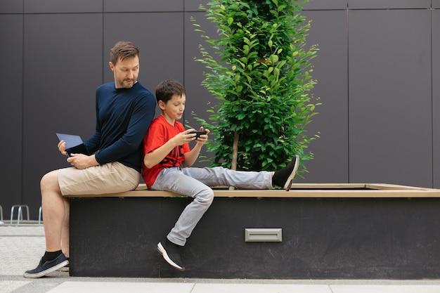 Tata i syn wśród betonowych konstrukcji używają modowych urządzeń do wspólnego spędzania czasu, grania w gry online, koncepcja nowoczesnego rodzicielstwa