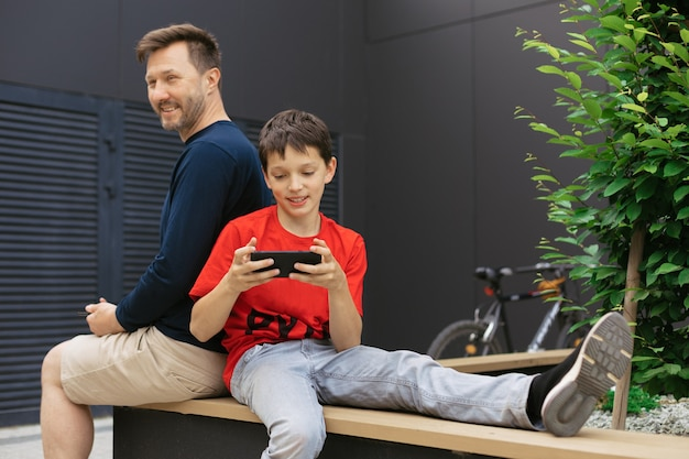 Tata i syn wśród betonowych konstrukcji używają modowych urządzeń do wspólnego spędzania czasu, grania w gry wideo online, koncepcja nowoczesnego rodzicielstwa