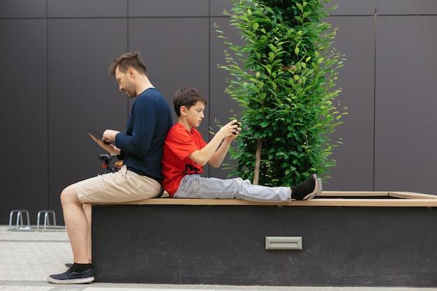 Tata i syn wśród betonowych konstrukcji używają modowych urządzeń do wspólnego spędzania czasu, koncepcji nowoczesnego rodzicielstwa