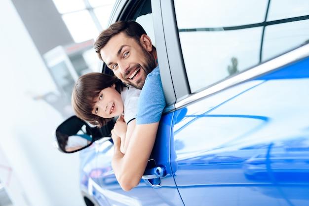 Tata i syn wyglądają przez okno nowo zakupionego samochodu.