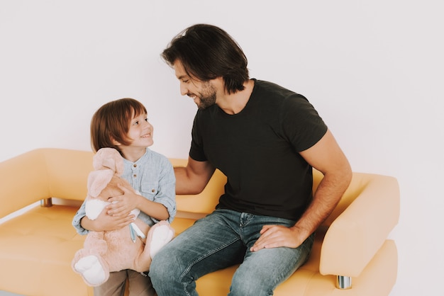Tata i syn z bunny toy w doctor waiting room.