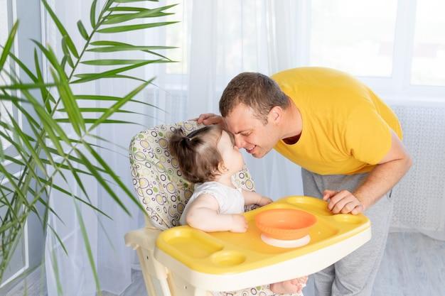 Tata karmi córeczkę w wysokim krzesełku, koncepcja jedzenia dla niemowląt, szczęśliwe ojcostwo