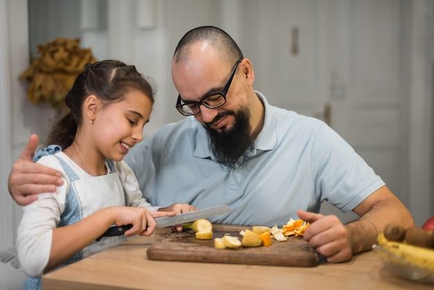 Tata karmi dziewczynę bananem w kuchni, jedzenie dla dzieci. jagody i owoce.