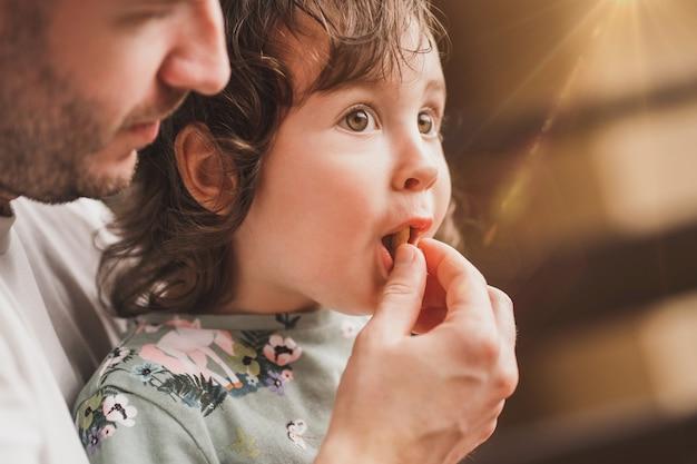 Tata karmi swoje dziecko orzechową silną więzią między tatą a córką, opieką nad dzieckiem przez ojca