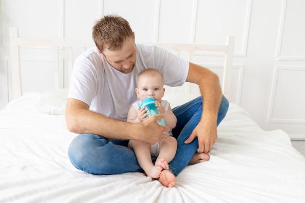 Tata karmi synka z butelki w domu, szczęśliwe ojcostwo, koncepcja jedzenia dla niemowląt
