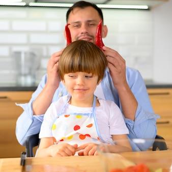 Tata kładzie paprykę kapia na głowie dziecka