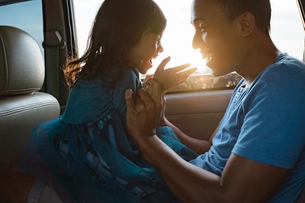 Tata łaskocze swoją małą dziewczynkę w samochodzie