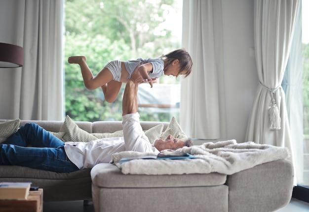 Tata leżący na sofie i unoszący swoje dziecko w powietrzu w słońcu wpadającym przez okna