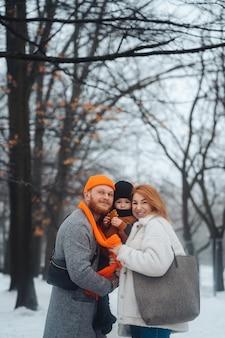 Tata mama i dziecko w parku w zimie