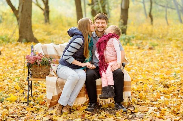 Tata, mama i ich córka siedzą na ławce w jesiennym parku. rodzice z małą dziewczynką schronili się w kocu, aby się ogrzać.
