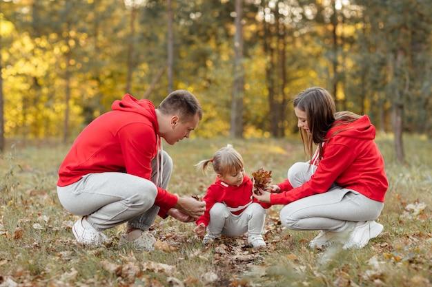 Tata, mama i mała śliczna córeczka bawią się i bawią w jesiennym parku.