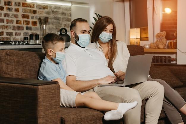 Tata, mama i syn siedzą na kanapie w maskach na twarz, aby uniknąć rozprzestrzeniania się koronawirusa (covid-19). krewni podczas kwarantanny w domu. ojciec pracuje zdalnie na laptopie w pobliżu swojej rodziny.