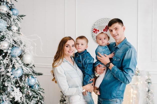 Tata, mama przytulają synka i córkę przy choince. wesołych świąt. boże narodzenie urządzone wnętrze. pojęcie wakacji rodzinnych. ścieśniać.