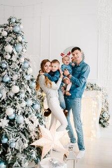 Tata, mama przytulająca syna i córkę w pobliżu choinki