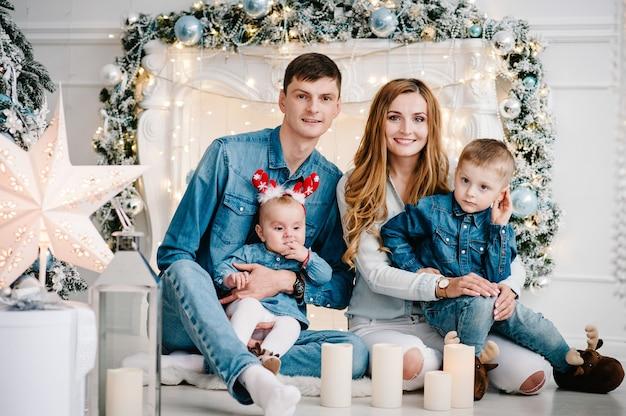 Tata, mama przytulająca synka i córkę w pobliżu choinki