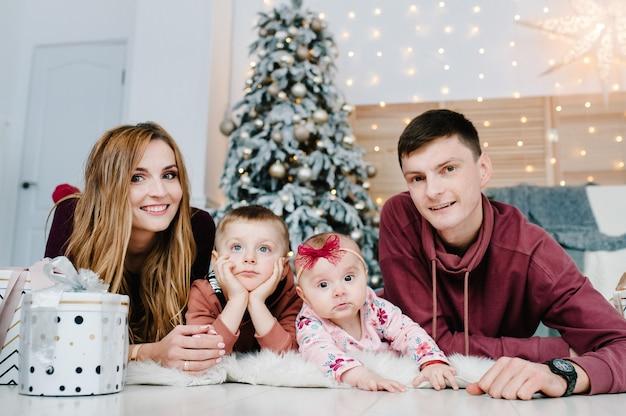 Tata, mama, synek i córka z prezentami na podłodze obok choinki