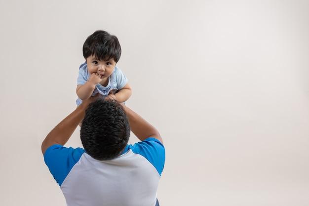 Tata niosący syna w powietrzu z rozpostartymi ramionami w dzień ojca