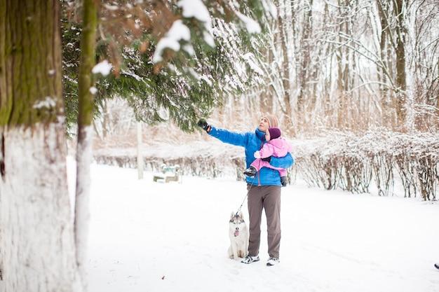 Tata pokazujący swoją uroczą córeczkę na śniegu