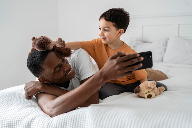 Tata pokazuje synowi coś przez telefon, świetnie się bawiąc