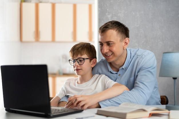 Tata pomaga synowi odrabiać lekcje. chłopiec odrabia lekcje z ojcem. tata uczy syna pracy z programem komputerowym.