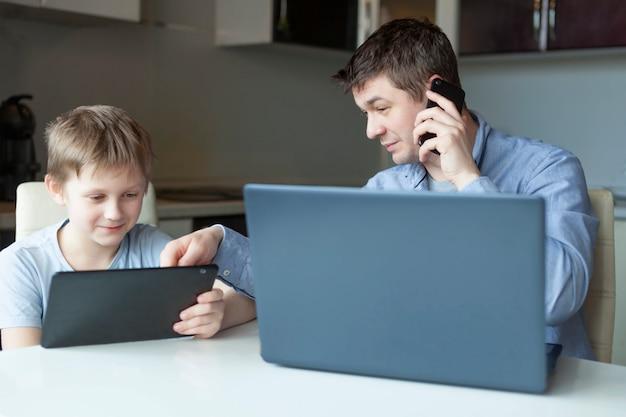 Tata pracuje z domu na laptopie. syn uczyć się z domu na tablecie. rodzina została razem w domu. koronawirus ochrona. więź, pojęcie przyjaźni.