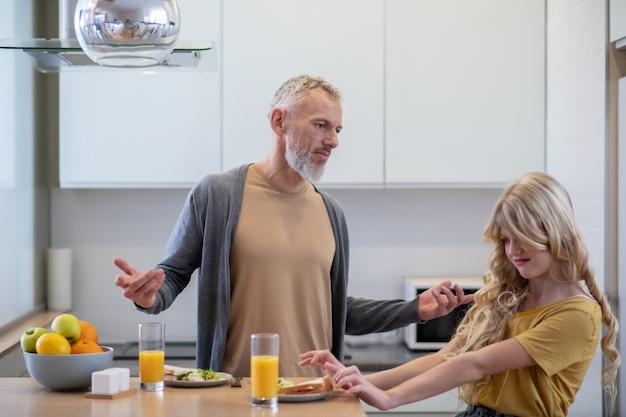 Tata próbuje zmusić córkę do jedzenia śniadania