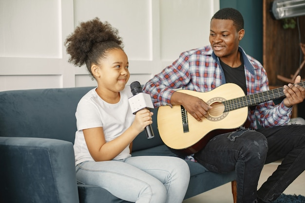 Tata siedzi z gitarą, a córka z mikrofonem