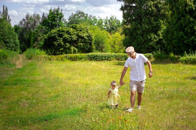 Tata spaceruje ze swoją małą córeczką na łące w okresie letnim