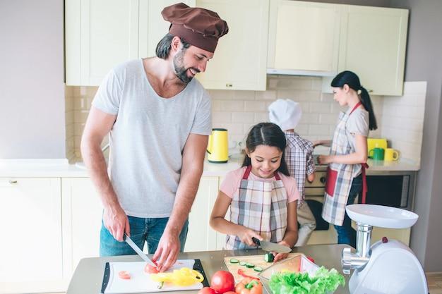 Tata stoi przy stole i kroi pomidora. jego córka stoi blisko i kroi ogórki. ona na to patrzy. facet robi to samo i uśmiecha się. kobieta stoi z synem przy kuchenką i kucharzem.