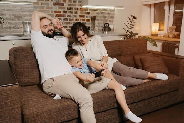 Tata, syn i mama na kanapie. szczęśliwe dziecko bawi się grą na smartfonie w pobliżu mamy i taty wieczorem w przytulnym domu.