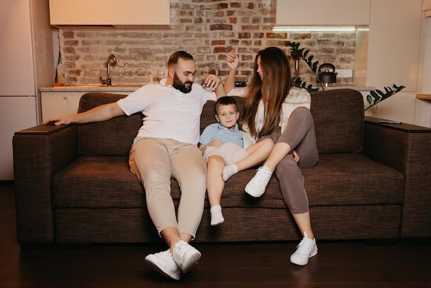 Tata, syn i mama oglądają na kanapie w mieszkaniu nudne programy telewizyjne. rodzice wpatrują się wieczorem w swojego chłopca. krewni w domu. uśmiecha się młoda matka z długimi włosami.