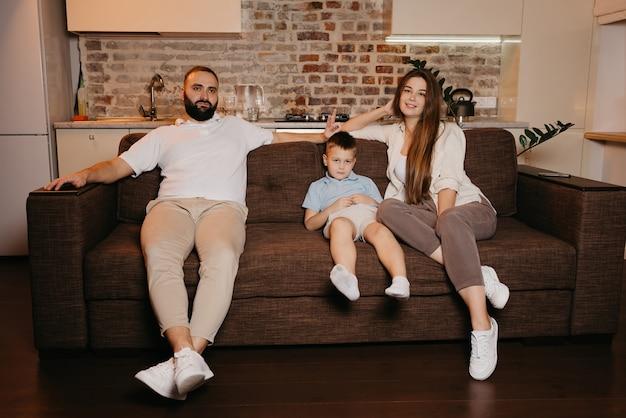Tata, syn i mama oglądają nudne programy telewizyjne na sofie w mieszkaniu