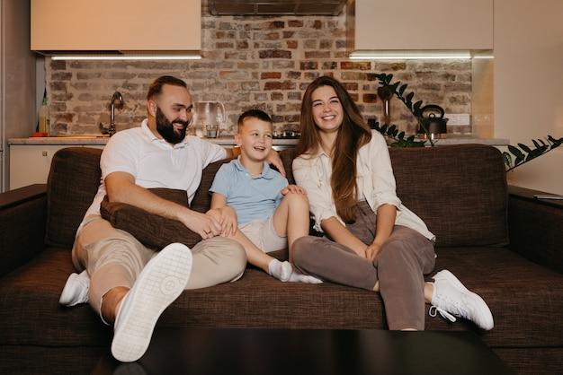Tata, syn i mama oglądają telewizję i śmieją się na kanapie w mieszkaniu. rodzina spędza szczęśliwy wieczór w domu. ojciec wpatruje się w swojego chłopca i żonę.