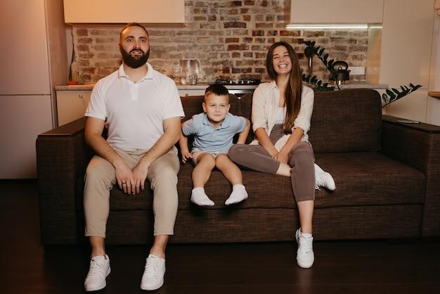 Tata, syn i mama oglądają telewizję na kanapie w mieszkaniu. rodzina cieszy się wieczorem. krewni w domu. śmieje się młoda matka z długimi włosami.