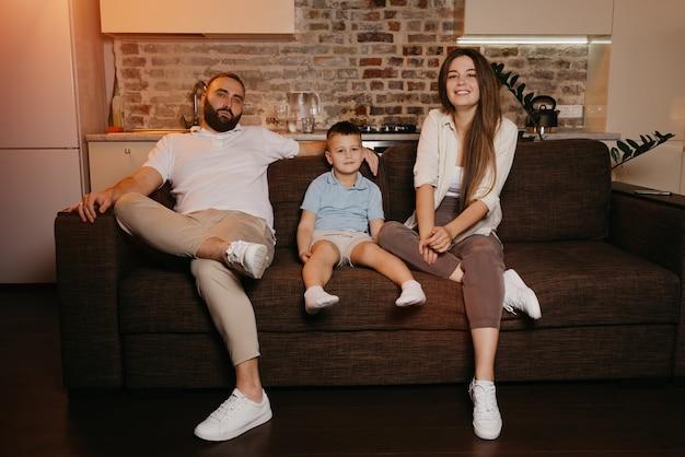 Tata, syn i mama oglądają telewizję na kanapie w mieszkaniu. rodzina cieszy się wieczorem. krewni w domu. uśmiecha się młoda matka z długimi włosami.